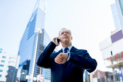 Senior businessman calling on smartphone in city. Business, technology, time, punctuality and people concept - senior businessman calling on smartphone with Royalty Free Stock Photography