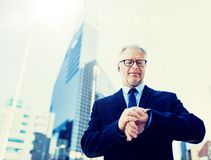 Senior businessman checking time on his wristwatch royalty free stock photography