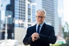 Senior businessman checking time on his wristwatch Stock Photos