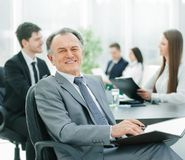 Senior businessman with a clipboard on the background of the office stock photos