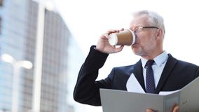 Senior businessman with coffee and folder in city. Business, hot drinks, office work and people and concept - senior businessman with ring binder folder drinking stock video
