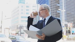 Senior businessman with coffee and folder in city. Business, hot drinks, office work and people and concept - senior businessman with ring binder folder drinking stock footage