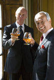 Senior businessman and colleague with drinks, smiling, portrait Royalty Free Stock Photo