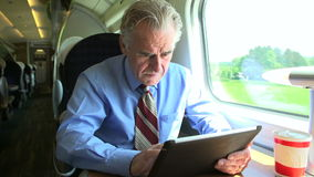 Senior Businessman Commuting On Train Using Digital Tablet Stock Photography
