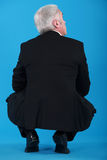 Senior businessman crouching Stock Photo