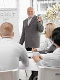 Senior businessman doing presentation. To team, gesturing and smiling, standing at whiteboard Stock Photos