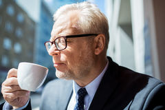 Senior businessman drinking coffee on city street. Business, hot drinks, break and people and concept - senior businessman drinking coffee from cup on city Stock Photography