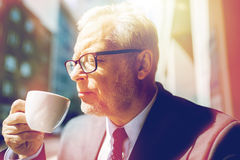 Senior businessman drinking coffee on city street. Business, hot drinks, break and people and concept - senior businessman drinking coffee from cup on city Stock Photo