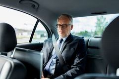 Senior businessman driving on car back seat Stock Images