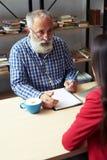 Senior businessman explaining something and writing Stock Photography