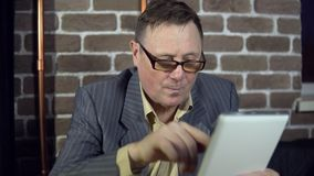 Businessman uses a digital tablet in a room with a brick wall. Senior businessman in eyeglasses is working with a digital tablet at the office with a brick wall stock footage