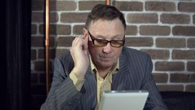 Businessman uses a digital tablet in a room with a brick wall. Senior businessman in eyeglasses is working with a digital tablet at the office with a brick wall stock video