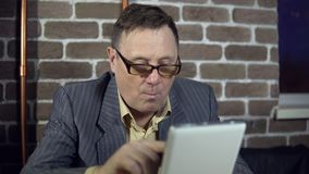 Businessman uses a digital tablet in a room with a brick wall. Senior businessman in eyeglasses is working with a digital tablet at the room with a brick wall stock footage