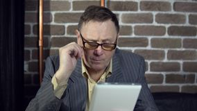Businessman uses a digital tablet in a room with a brick wall. Senior businessman in eyeglasses is working with a digital tablet at the room with a brick wall stock video footage