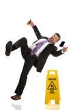 Senior Businessman Falling on Wet Floor. Hispanic businessman falling next to wet floor sign isolated over white background Royalty Free Stock Photo