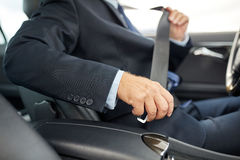 Senior businessman fastening car seat belt. Transport, business trip, safety and people concept - senior businessman fastening seat belt before driving car royalty free stock photo