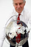 Senior businessman with globe Stock Photography