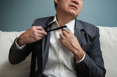 Senior businessman in grey suit adjusting his tie. Tired, Exhaus Royalty Free Stock Photo