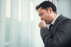 Senior businessman in grey suit coughing. Illness, disease, alle Stock Image