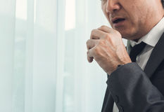 Senior businessman in grey suit coughing. Illness, disease, alle Royalty Free Stock Image