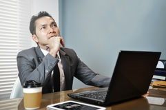 Senior Businessman in grey suit sitting and thinking on his work Stock Image