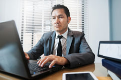 Senior Businessman in grey suit sitting and using laptop at his Stock Photos