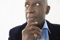 Senior Businessman With Hand On Chin. Closeup of an African American senior businessman with hand on chin against white background Royalty Free Stock Photography