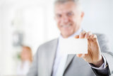 Senior Businessman. Happy senior businessman holding Blank business card in the office. Looking at camera. Selective Focus. Focus on business card Stock Photos