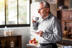 Senior businessman having coffee in kitchen at home stock photography