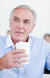 Senior businessman holding a drinking cup Stock Photo