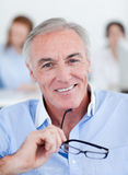 Senior businessman holding glasses Stock Photo