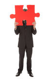 Senior businessman holding a jigsaw puzzle Royalty Free Stock Images