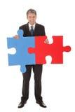 Senior businessman holding a jigsaw puzzle Stock Photography