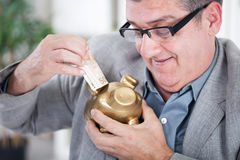 Senior businessman inserting money to a piggy bank Royalty Free Stock Image