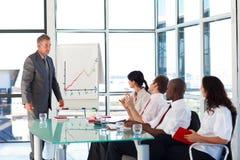 Senior businessman interacting with his team Stock Photo