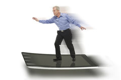 Senior businessman keeping balance on a PC tablet Royalty Free Stock Images