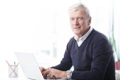 Senior businessman with laptop Stock Photos