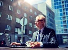Senior businessman with laptop drinking coffee stock image