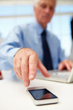 Senior businessman with laptop and phone Stock Photography