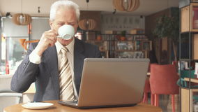 Senior businessman looking at the laptop screen. Senior gray businessman looking at the laptop screen at the cafe. Aged caucasian man dressed in suit and tie