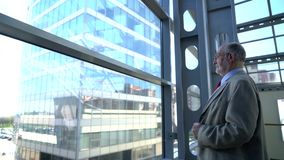 Senior businessman looking at window stock video footage