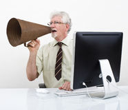 Senior businessman megaphone. Senior businessman using a retro megaphone in front of computer Stock Photography