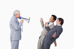 Senior businessman with megaphone yelling. At his employees against a white background Royalty Free Stock Images