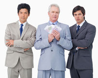 Senior businessman with money standing between his employees Stock Photo