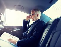 Senior businessman with papers driving in car royalty free stock image