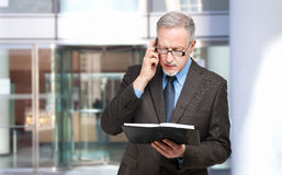 Senior businessman at the phone. Looking his agenda Stock Photography