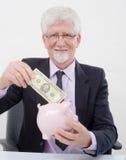 Senior businessman and piggybank. Senior businessman inserting a 100 dollar bill to  a piggy bank Stock Photography