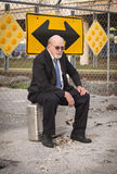 Senior Businessman Ponders Which Way to Go. Defeated homeless senior businessman sits on suitcase near railroad train tracks under a directional sign, pondering Stock Photography