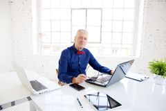 Senior businessman portrait while working on laptops in the office stock image