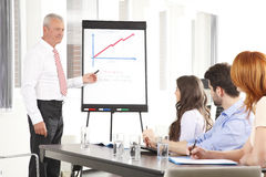 Senior businessman presenting ideas to his business team Stock Photos